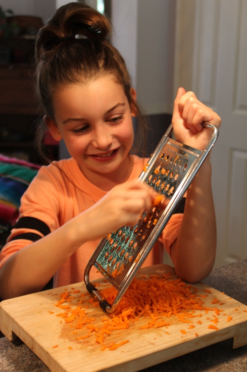 Charlotte râpe les carottes
